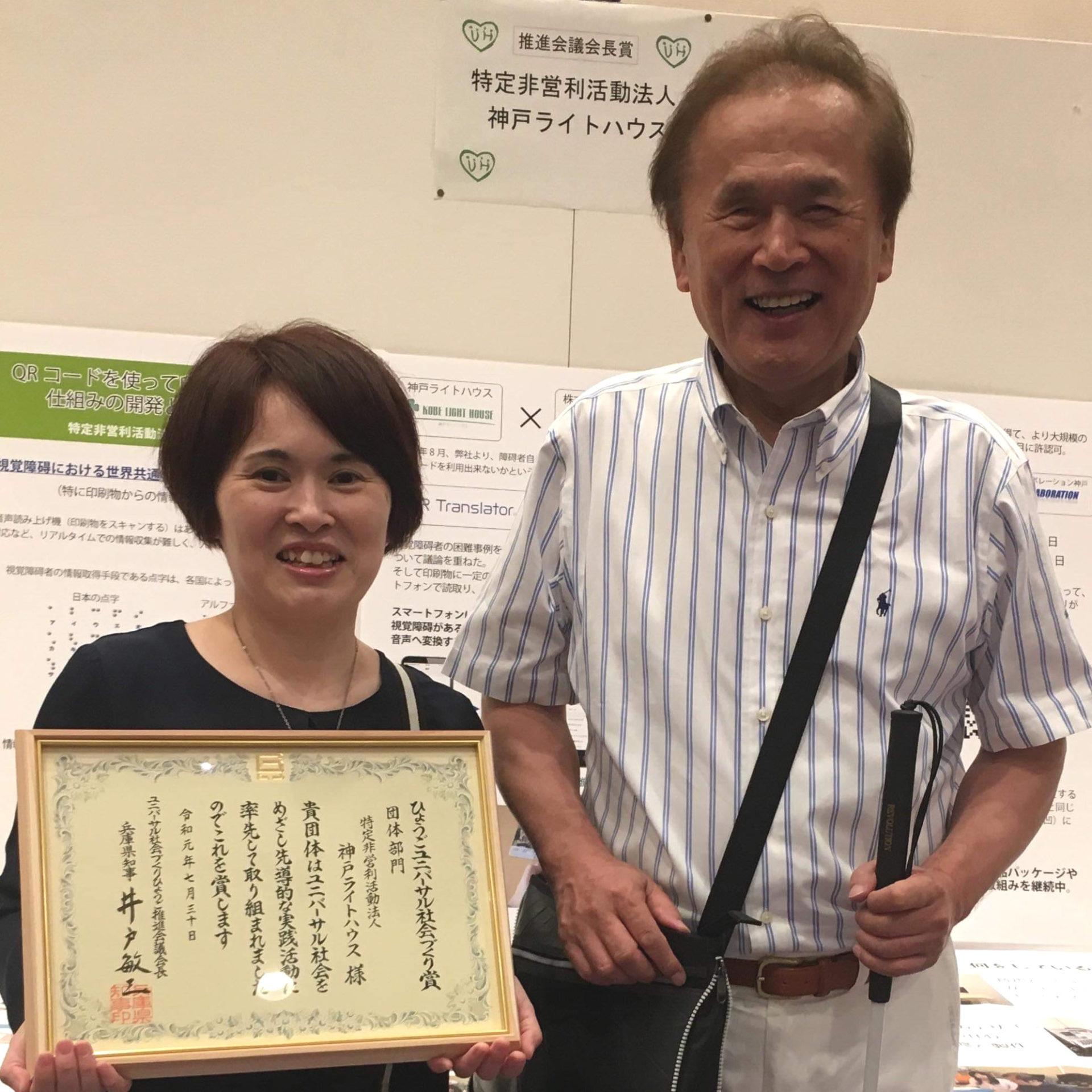 太田氏と和田氏の顔写真、ひょうごユニバーサル社会づくり賞の賞状を持っている。