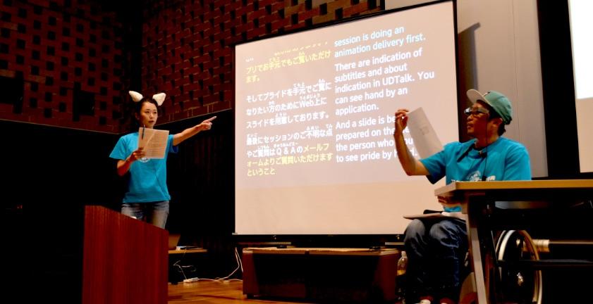 写真:セッションのようす。車椅子の登壇者と猫耳をつけた登壇者がステージの上で話している。スクリーンには字幕が表示されている。